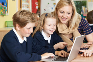 connectEd learning: Image shows teacher and pupils at computer