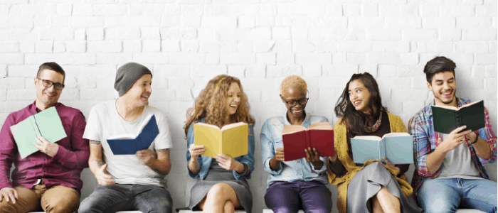 Group of young adults reading books and laughing
