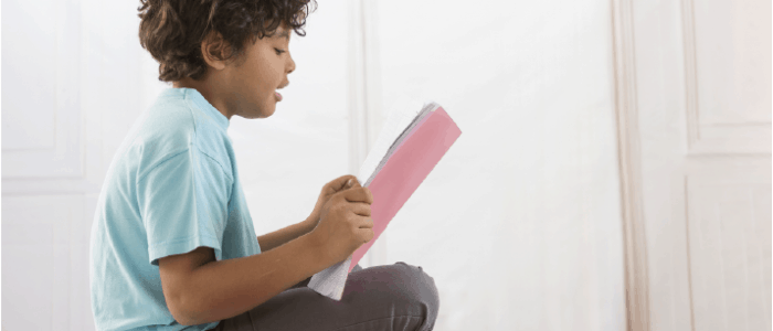 Child reading a pink notebook