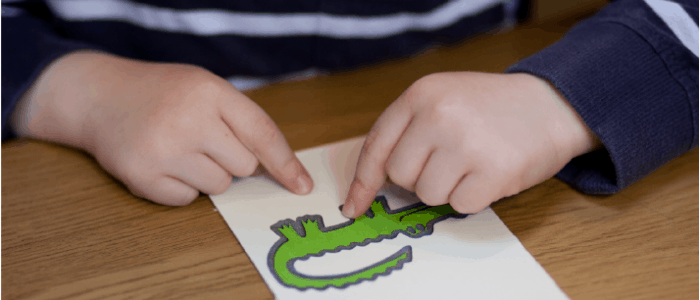 children feeling a tactile image of a crocodile